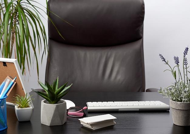 Table noire avec papeterie, clavier sans fil, souris, lieu de travail d'un leader