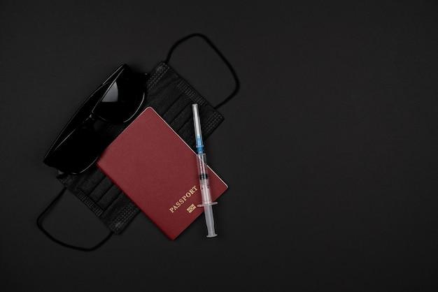 Sur une table noire, un passeport, des lunettes noires, un masque médical noir et une seringue. concept de voyage de quarantaine