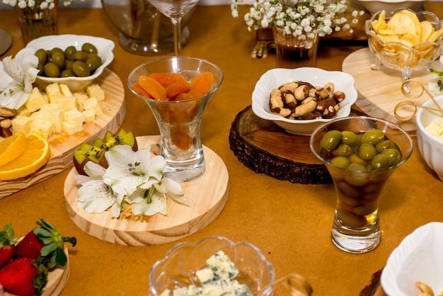 Table avec nourriture, abricot, olive, châtaigne et fromage.