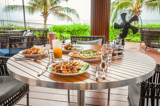 Table avec nourriture et cocktails dans un restaurant en plein air dans un complexe tropical ou un hôtel