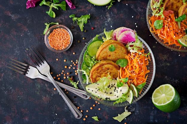 Table de nourriture de dîner de bol de bouddha végétalien. nourriture saine. bol déjeuner végétalien sain. beignet aux lentilles et radis, avocat, salade de carottes. mise à plat.