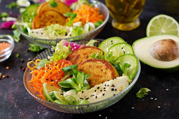 Table de nourriture de dîner de bol de bouddha végétalien. nourriture saine. bol déjeuner végétalien sain. beignet aux lentilles et radis, avocat, salade de carottes.