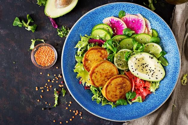 Table de nourriture de dîner de bol de bouddha végétalien. nourriture saine. bol déjeuner végétalien sain. beignet aux lentilles et radis, salade d'avocat. mise à plat.