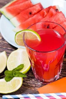 Une table avec de la nourriture et des pastèques mûres rouges à partir de laquelle un jus de pastèque délicieux et sain est fait