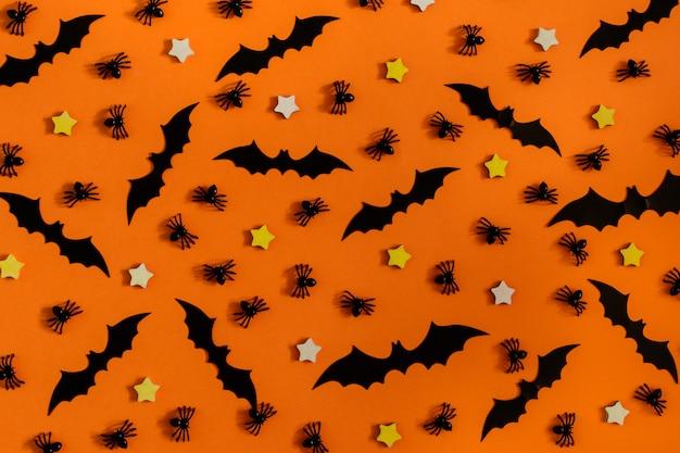 Sur la table orange disposées de nombreuses araignées décoratives, petites étoiles et chauves-souris.