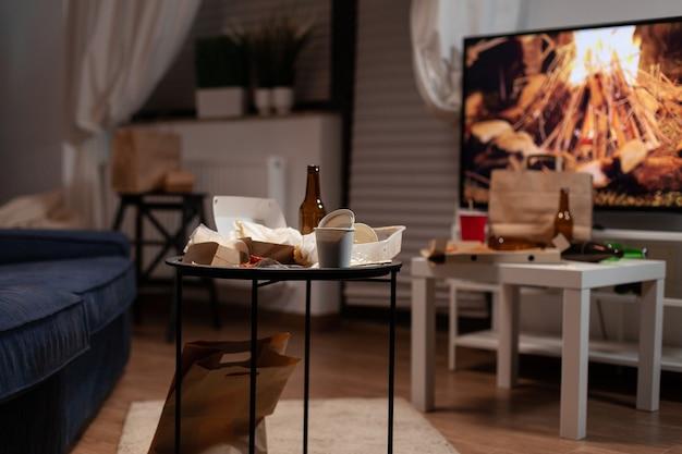 Table à ordures avec bouteille de bière vide et déchets alimentaires placés dans le salon