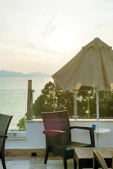 Une table en osier confortable dans le café-bar en plein air sur le toit au coucher du soleil