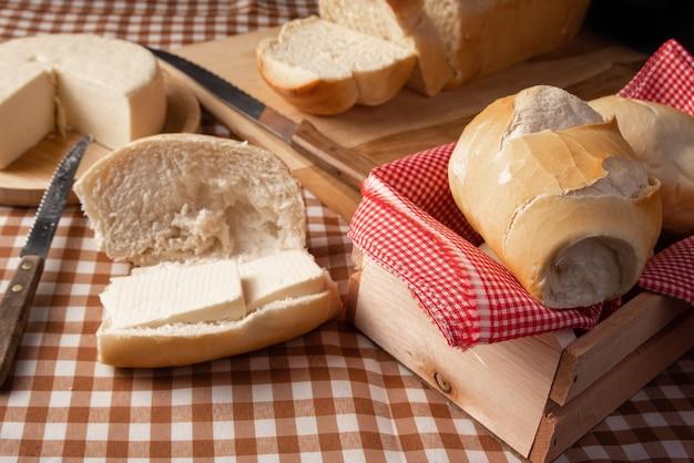 Table de petit-déjeuner au brésil avec pains, fromage, tasse de café et accessoires sur une nappe à carreaux marron et beige.