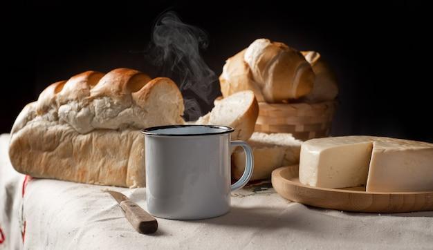 Table de petit-déjeuner au brésil avec pains, fromage, tasse de café et accessoires sur une nappe légère avec broderie.