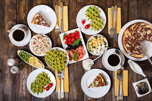 Table de petit déjeuner. ensemble de brunch festif, variété de repas avec gaufres aux épinards, saumon, fromage, olives, rouleaux de poulet et gâteau au fromage. vue de dessus. mise à plat