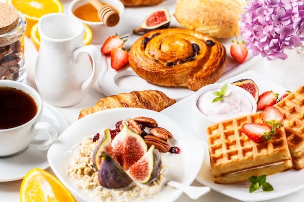 Table de petit déjeuner avec des flocons d'avoine, des gaufres, des croissants et des fruits.