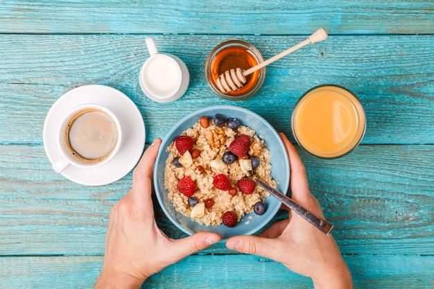 Table de petit déjeuner avec gaufres, flocons d'avoine, céréales, café, jus de fruits et baies fraîches