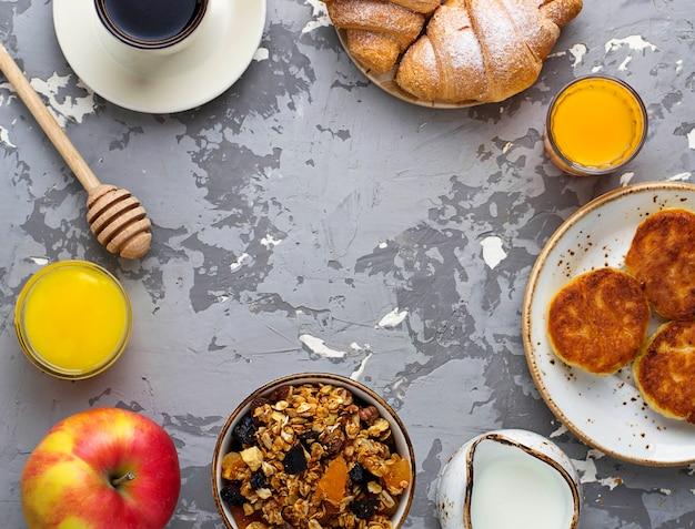Table de petit déjeuner avec granola, croissants, pomme, café, jus de fruits.