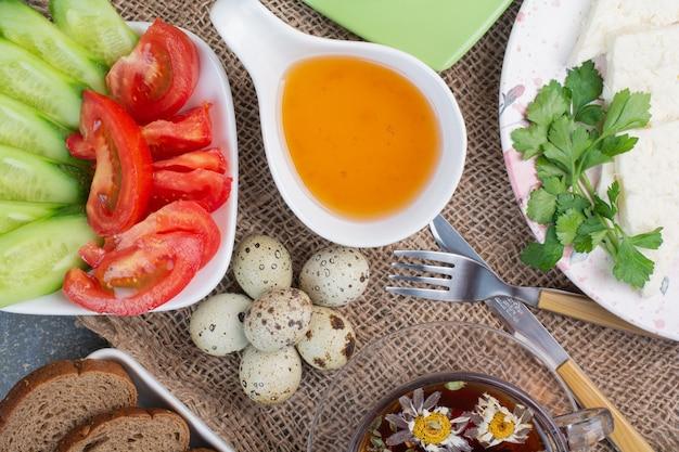 Table de petit-déjeuner avec légumes, thé, pain et œufs