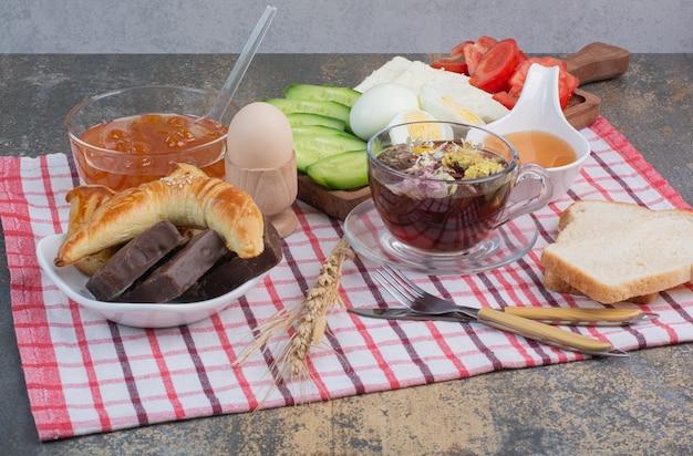 Table de petit-déjeuner avec nourriture, desserts et thé