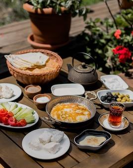 Table de petit déjeuner avec omelette, fromage, olives et légumes.