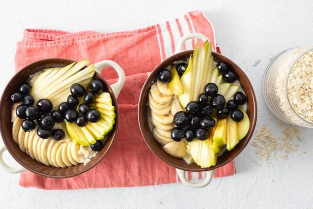 Table de petit déjeuner sain. plaque avec flocons d'avoine et poire, pomme, myrtille, banane sur une vue de dessus blanche