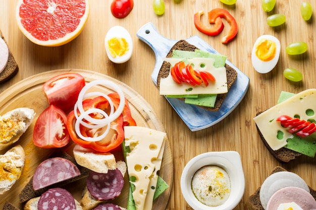 Table de petit-déjeuner avec sandwiches au fromage, saucisses, légumes, œufs durs et fruits. vue de dessus