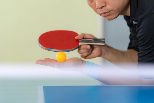 Table de ping-pong, homme jouant au tennis de table avec raquette et balle dans une salle de sport