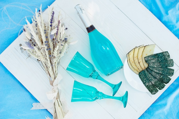 Table de pique-nique en bois blanc avec une bouteille de champagne bleu et des assiettes avec différents fromages, concept pour une fête ou un pique-nique saisonnier en plein air ou de vacances.