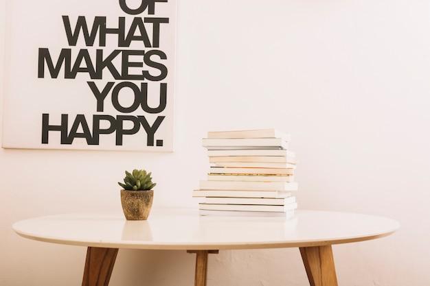 Table avec plante et livres près du mur