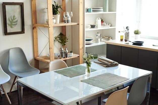 Table en plastique rectangulaire blanche avec bouquet de fleurs sauvages dans un vase entre deux serviettes grises au centre d'une pièce ou d'une cuisine domestique moderne