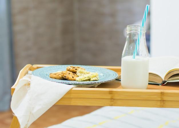 Table plateau de lit, avec du lait, des biscuits et un livre.