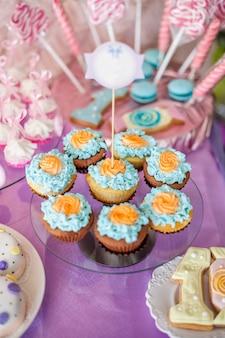 Table pour enfants avec cupcakes avec dessus bleu et orange et objets de décoration en rose vif et bleu