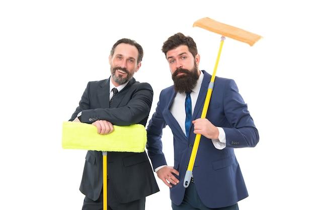 Table rase. entreprise de nettoyage. entreprise propre. partenariat et travail d'équipe. des hommes barbus matures en costume formel tiennent une vadrouille domestique. les hommes d'affaires effacent le mur au blanc. je t'ai préparé une surprise.