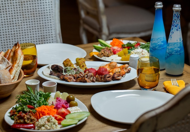 Table de repas offerte avec une variété d'aliments et deux bouteilles d'eau minérale bleue.