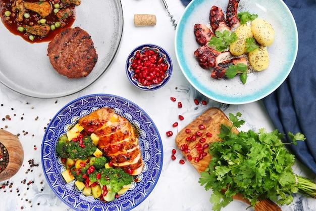Table avec repas de viande et salade. poulpe aux pommes de terre et poulet à la mangue, galette de viande aux pois et ingrédients sur la vue de dessus de table.