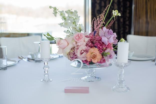 Table de restaurant blanche de l'événement servie et décorée de délicates fleurs fraîches.