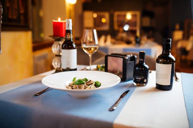 Table de restaurant servie avec tagliatelles aux champignons sauvages dans une assiette blanche