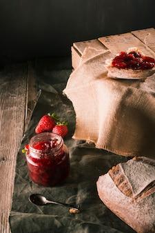 Table avec des restes de petit-déjeuner et des confitures de fraises