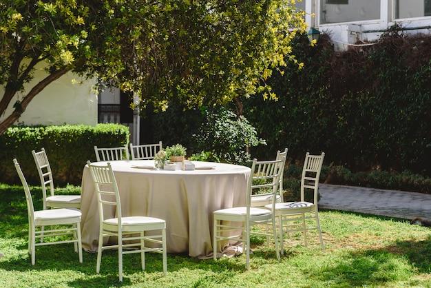 Table ronde avec des nappes blanches et des chaises pour une ouverture en extérieur