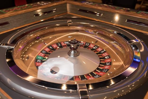 Table de roulette au casino, avec de nombreux jeux et machines à sous, roulette au premier plan. lumière dorée et luxueuse, intérieur de casino. le jeu consiste à parier de l'argent ou à jouer à des jeux de hasard pour de l'argent