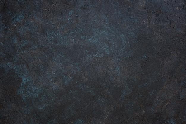 Table rugueuse foncée texturée avec des taches bleues et jaunes