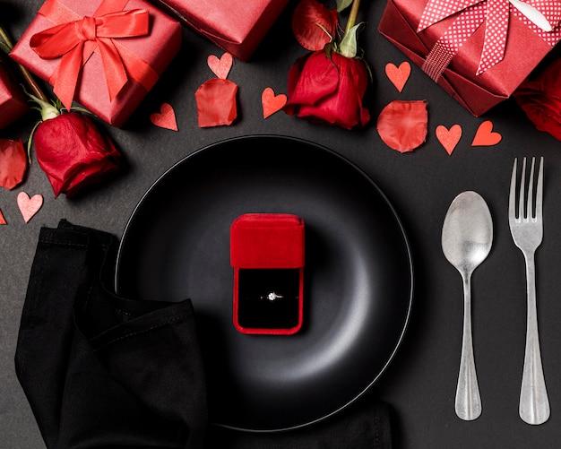 Table de la saint-valentin avec bague de fiançailles sur assiette et roses