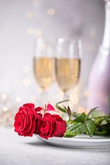 Table de la saint-valentin, roses rouges et verres de champagne sur fond de béton. carte de voeux de la saint-valentin - image