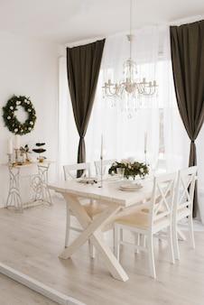 Table de salle à manger en bois blanc avec chaises dans un salon lumineux décoré pour noël et le nouvel an dans un style classique