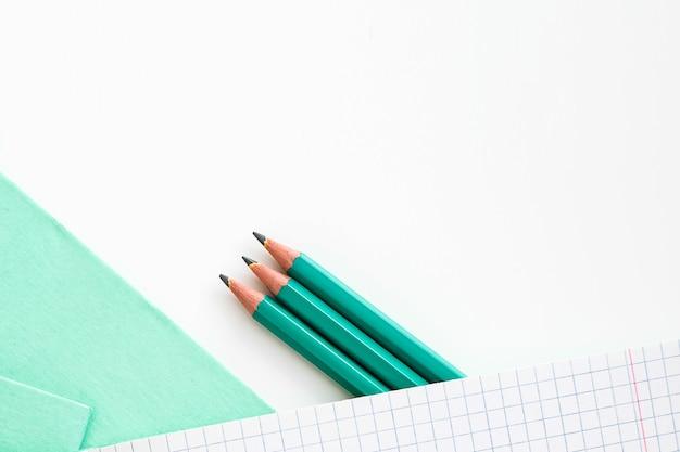 Sur la table se trouve un cahier ouvert dans une cage. crayons à côté du cahier d'école. cahier d'école