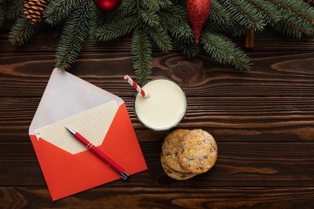 Sur la table se trouve une enveloppe avec une lettre ainsi que du lait et des biscuits faits maison laissés pour le père noël