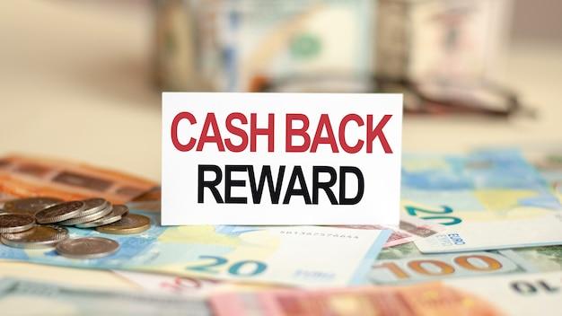 Sur la table se trouvent des billets de banque, des pièces de monnaie et un signe sur lequel il est écrit - récompense en argent. concept de finances et d'économie.