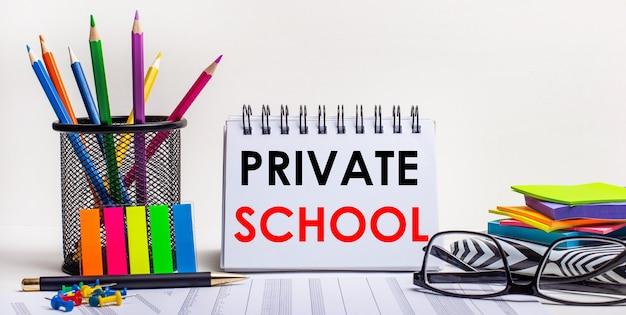 Sur la table se trouvent des crayons de couleur dans un support, des autocollants aux couleurs vives, des lunettes et un cahier avec l'inscription private school. concept motivant