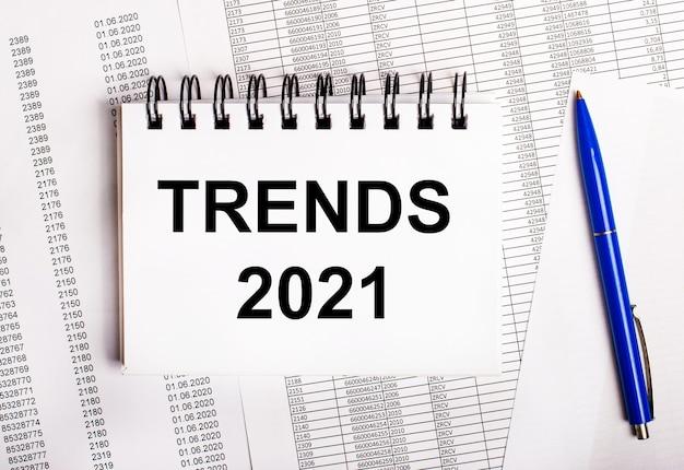 Sur la table se trouvent des graphiques et des rapports sur lesquels se trouvent un stylo bleu et un cahier avec le mot tendances 2021