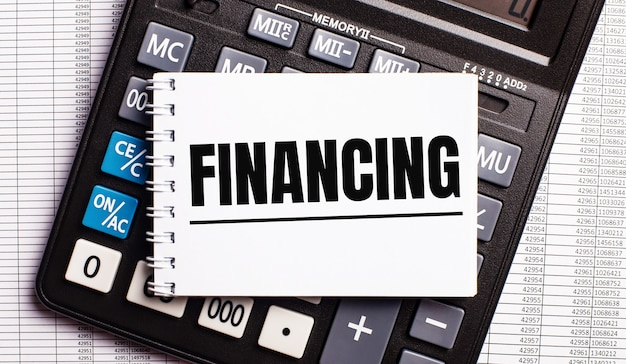 Sur la table se trouvent des rapports, une calculatrice et une carte avec le mot financement dessus. concept d'entreprise