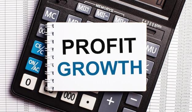 Sur la table se trouvent des rapports, une calculatrice et une carte avec les mots profit growth dessus