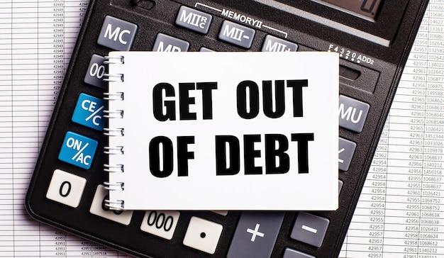 Sur la table se trouvent des rapports, une calculatrice et une carte avec les mots sortir de la dette. concept d'entreprise