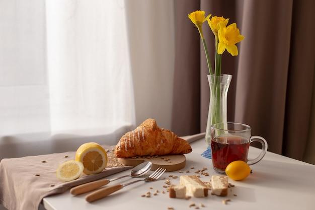 Table servant le petit déjeuner avec une tasse de thé, des croissants, des citrons et des narcis jaunes dans un vase en verre