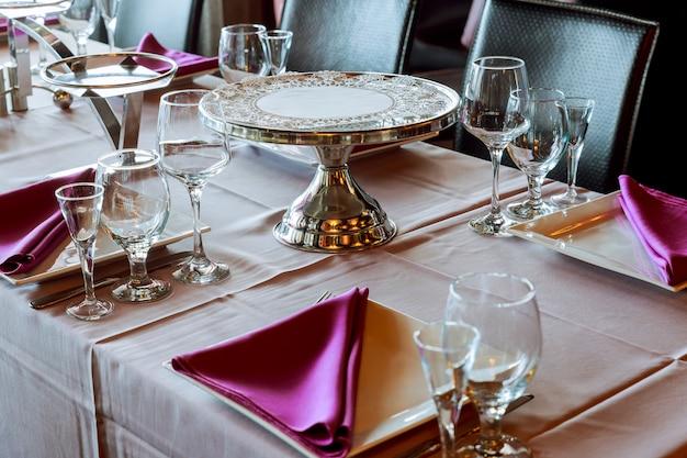 Table de service au restaurant avec verres à vin et couverts.
